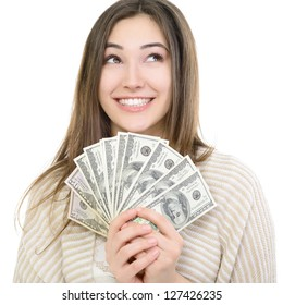 Cheerful attractive young smiling woman holding cash, dreaming and looking up over white