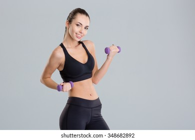 Cheerful attractive young sportswoman lifting dumbbells over grey background