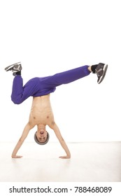Cheerful attractive young topless male dancer sitting upside down on his hands, performing streetdance position , wearing ultraviolet pants, with legs up and apart. Vertical image in studio, on white