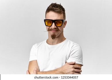 Cheerful attractive young unshaven male with stylish hairdo, goatee beard and handlebar mustache being in good mood, crossing arms on his chest and smiling confidently, wearing trendy spectacles