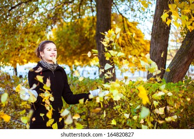 Cheerful attractive young woman in autumn park