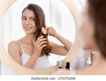 Cheerful attractive young woman combing hair in front of mirror at home