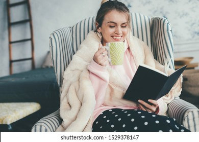 Cheerful attractive young woman sitting in chair and reading book. Also drink coffee or tea from cup and smile. Homie cozy look. Alone in room. Relaxed day