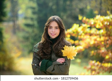 Cheerful autumn woman with long healthy hair holding red maple leaf outdoors in sunny day. Beautiful girl in fall park