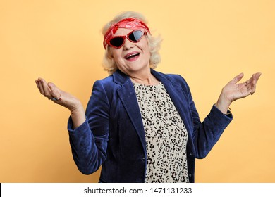 cheerful awesome cool granny with raised hands looking at camera. isolated yellow background, studio shot