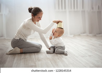 Cheerful baby boy having fun with mother on floor, Mum gently embraces the blond son and laughing in real light interior