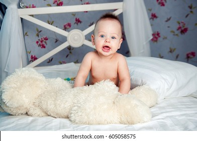 Cheerful baby boy  in the  sailor white-blue striped cap and shorts