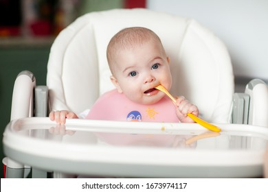 Cheerful baby child eats food itself with spoon. Portrait of happy kid girl in high chair.