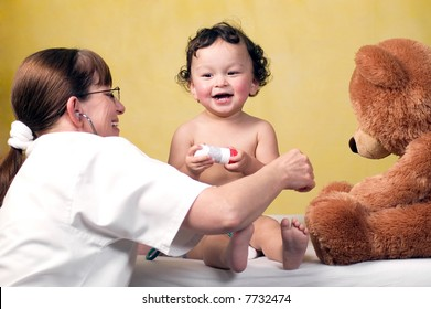 Cheerful baby at the doctor,playing with toy bear.