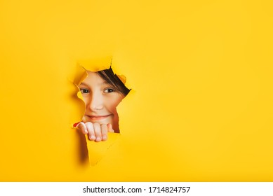 Cheerful baby girl face looks out through torn hole in yellow paper wall. Peek through hole. Discover something new. Looking beyond. Aside place for text information, advertising, positive news.