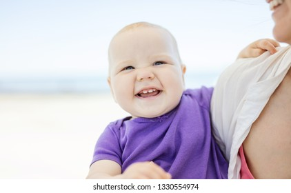 Cheerful baby girl in mother's arms on beach