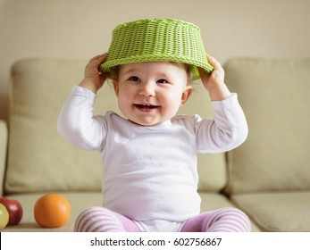 Cheerful baby girl plays with fruits at home. One-year-old child puts a fruit basket on his head like a hat. A funny smiling baby is naughty. Portrait of a cute playful baby.
