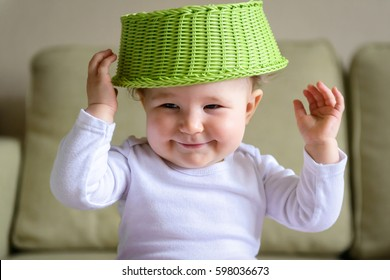 Cheerful baby puts a fruit basket on his head like a hat. One-year-old child plays at home. Cute baby girl is naughty and smiling. Portrait of a playful kid.