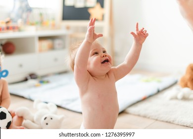 Cheerful baby reaching out to his mum