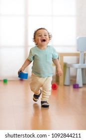 Cheerful baby toddler running in children room