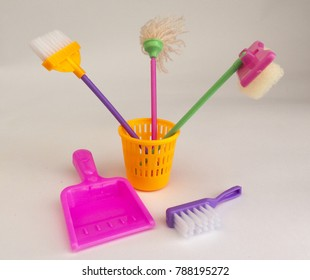Cheerful background with a toy cleaning tools - broom, shovel, bucket, broom, brush