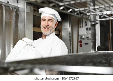 Cheerful baker. Smiling, happy cook carries a sack of flour