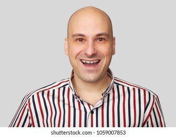 Cheerful bald guy smiles happily. Man is smiling, isolated over gray studio background. People emotions concept