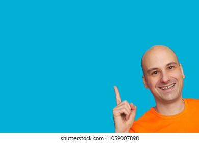 Cheerful bald man indicates with his finger upwards to copy space. Happy smiling guy in bright orange shirt isolated on blue background