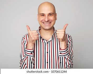 cheerful bald man. Middle aged guy showing thumbs up. isolated over grey studio wall