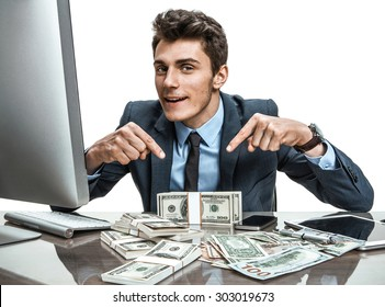 Cheerful banker showing his dividend profit, income, earnings, gain, benefit, margin / modern businessman at his desk with computer and a lot of money