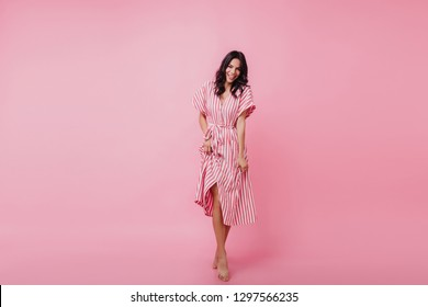Cheerful barefooted girl posing with happy smile. Indoor portrait of blissful black-haired woman dancing on pink background