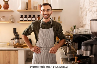 Cheerful barista. Cheerful dark-haired bearded barista smiling while welcoming guests