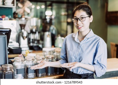 Cheerful barista showing coffee varieties and offering to buy tasty coffee. Positive young Asian restaurant manager presenting coffee. Drink establishment concept