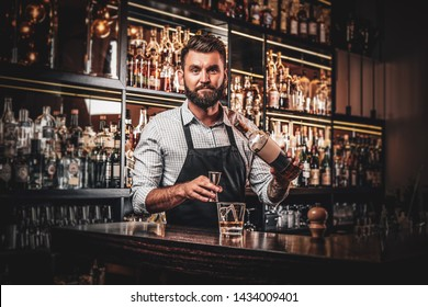 Cheerful barman is making beverage for customers at cozy restauraunt.
