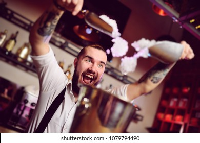 cheerful barman smiles, screams and falls asleep in a bucket for champagne on the background of the bar. Nightlife, bartender show.