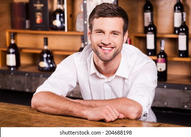 Cheerful bartender. Handsome young male bartender in white shirt leaning at the bar counter and smiling
