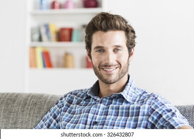 Cheerful bearbed hipster man in white modern house. Face camera