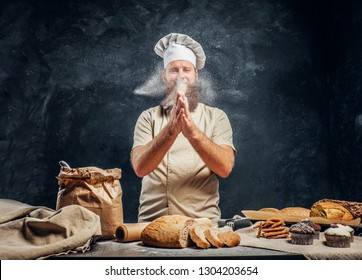 Cheerful bearded baker claps his hands with flour over the table with freshly prepared products from his bakery