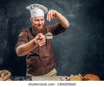 Cheerful bearded baker sprinkling some flour on his freshly made muffin next to a table in a dark studio