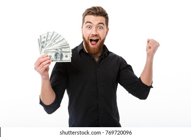 Cheerful bearded business man in shirt holding money and looking at the camera over white background