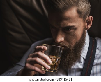 Cheerful bearded businessman is drinking expensive whisky