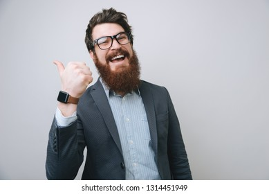 Cheerful bearded businessman in eyeglasses, thumbs up posing and smiling at camera