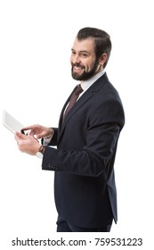 cheerful bearded businessman in suit using digital tablet, isolated on white