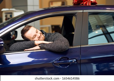 cheerful bearded client lying on the car, pretanding that he hugging vehicle, warm tender feeling, tenderness, best friend, friendship concept