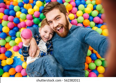 Cheerful bearded dad and little son talking selfie at pool with colorful balls