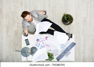 Cheerful bearded entrepreneur sitting at office desk and throwing documents in air after successful completion of promising project, directly above view