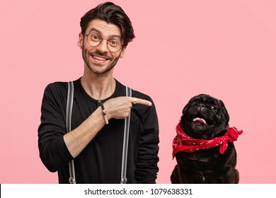 Cheerful bearded fashionable male model indicates with happiness at black dog wears red bandana on neck, feels proud of his clever pet, pose against pink studio wall. Advertisement and animals
