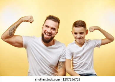 cheerful bearded father and son showing biceps and smiling at camera isolated on yellow
