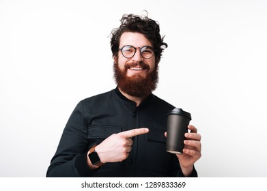 A cheerful bearded guy in glasses is pointig at cup of coffy or tea, standing over whote background