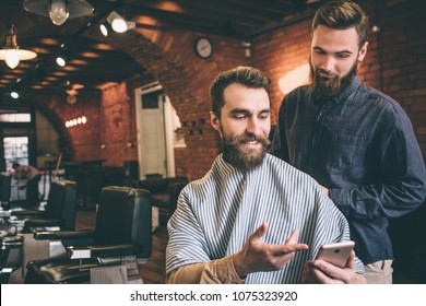 Cheerful and bearded guy is sitting in a chair and smiling. He is showing a picture to his hairdresser. The hairstylist is ready to do his job.