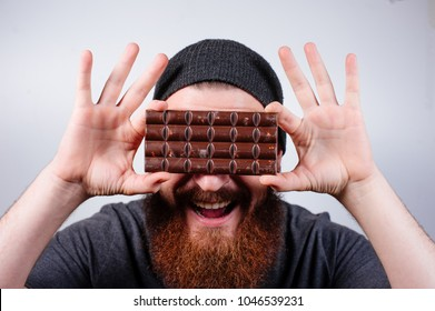 Cheerful bearded hipster man in hat holding chocolate on his eyes