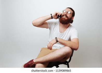 Cheerful bearded hipster man siting on chair and talking on phone