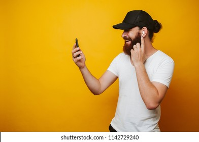 Cheerful bearded hipster man touching wireless earphones and looking at his smartphone over yellow background