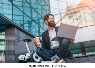 Cheerful bearded male entrepreneur with modern laptop and takeaway coffee smiling away while sitting on stairs with electric transport outside building on city street