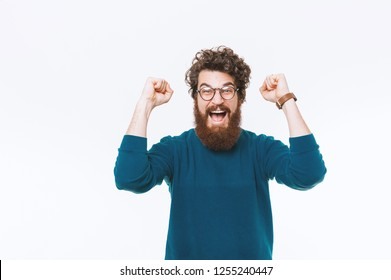 Cheerful bearded man celebrating success over white background